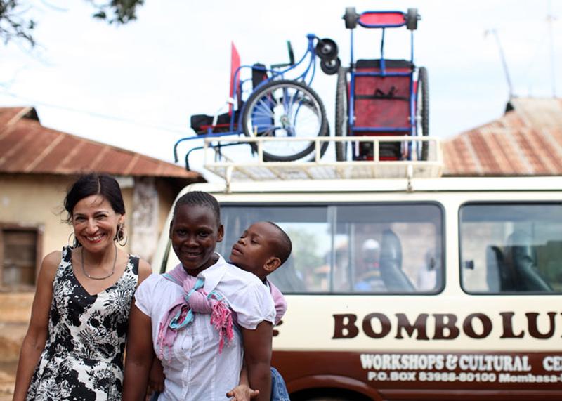 車椅子が必要な少年とその母親とサフィア。少年に届けた車椅子の前で撮影。